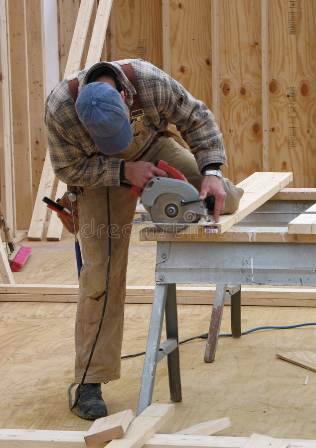 Carpenter using a circular saw royalty free stock images