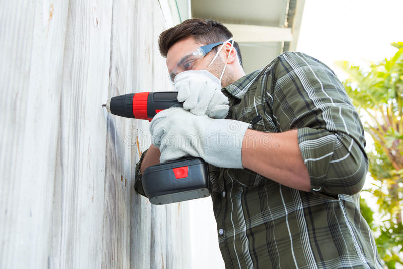 Carpenter using drill machine. Male carpenter using drill machine on wooden cabin stock photography