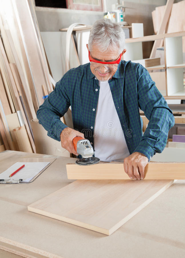 Carpenter Using Electric Sander At Table. Senior carpenter using electric sander on wood at table in workshop stock photo