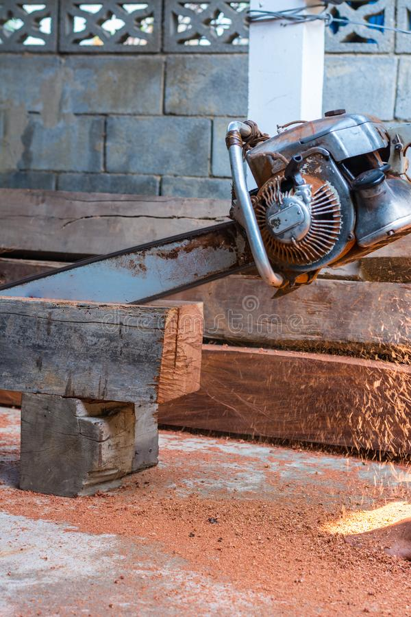Carpenter is using gasoline engine portable chainsaw cut timber royalty free stock image