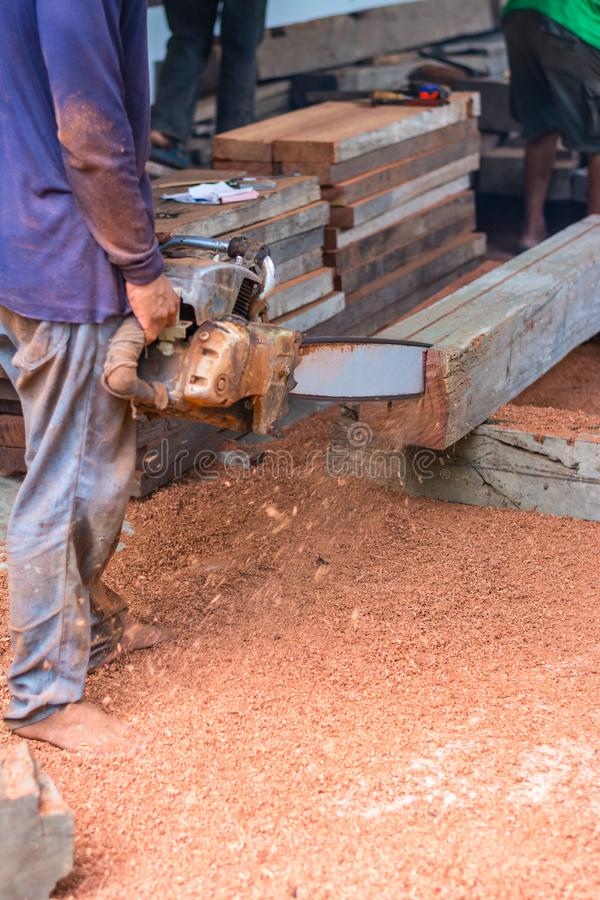 Carpenter is using gasoline engine portable chainsaw cut timber royalty free stock images