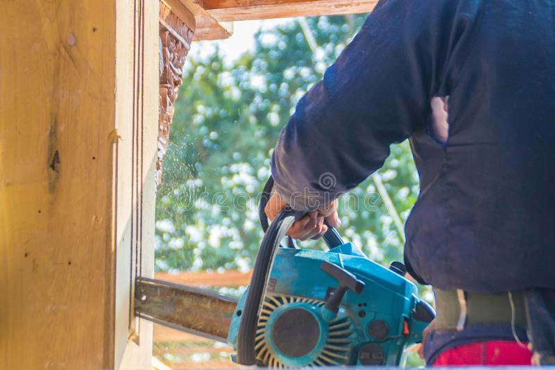 Carpenter is using gasoline engine portable chainsaw cut timber to vertical groove line. Hands of the carpenter using gasoline eng stock images
