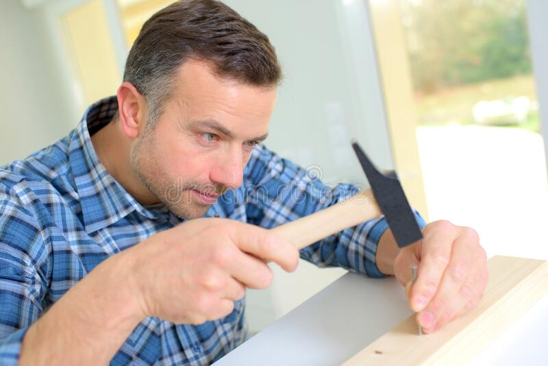 Carpenter using hammer stock photography