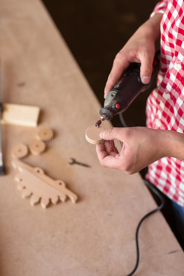 Carpenter Using a high speed rotary multi tool to cut a wooden. Master carpenter Woodworking engraving knife cutter grinder rotary rasp toy wooden dinosaur royalty free stock photo