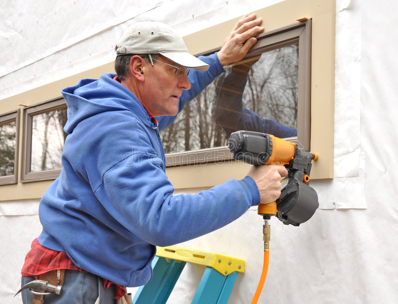 Carpenter using nail gun. To attach window trim royalty free stock images