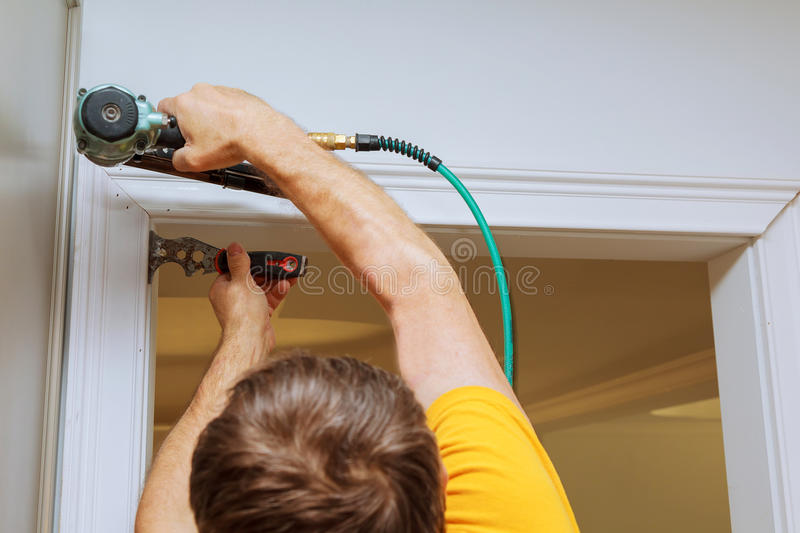 Carpenter using nail gun to moldings on windows, framing trim,. With the warning that all power tools have on them shown illustrating safety concept stock photography