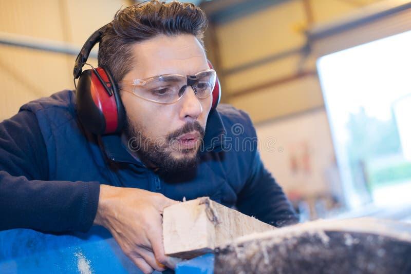 Carpenter using power-tool for cutting wood. Man stock photo