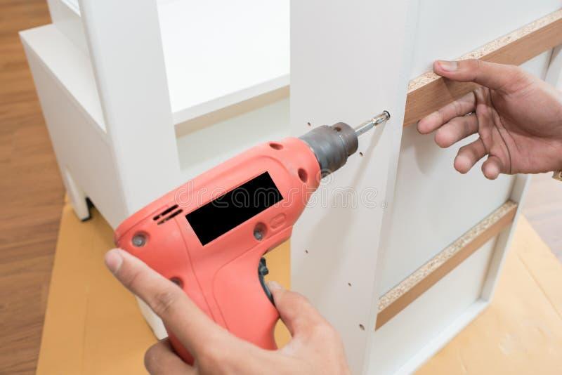 Carpenter using Screwdriver assemble furniture stock photo