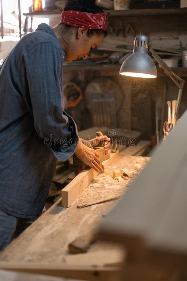 Carpenter woman in denim clothing works in a wood workshop stock photos