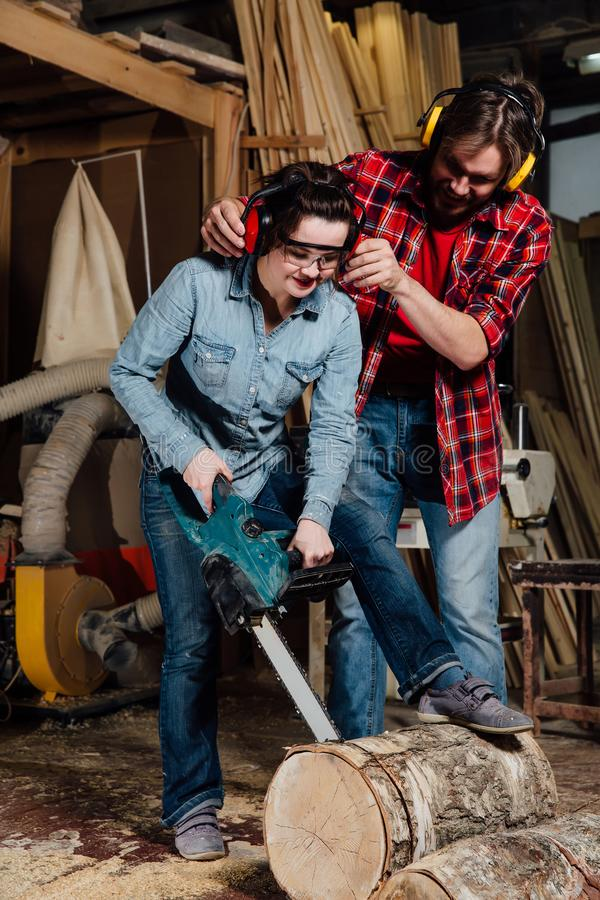 Carpenter woman and man with electric chainsaw in workshop. stock image