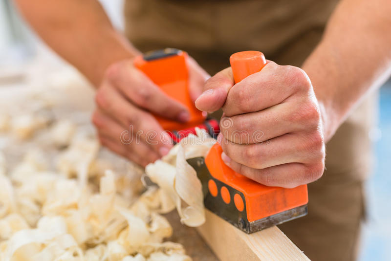 Carpenter with wood planer working on piece stock photo