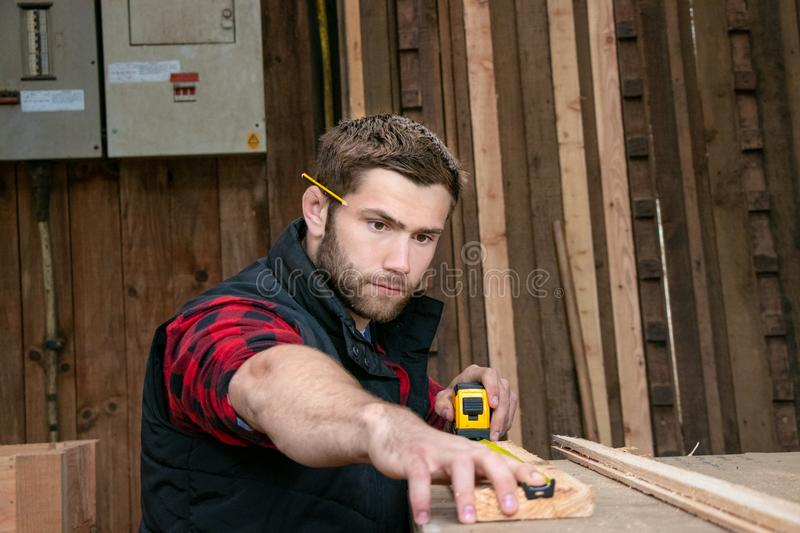 Carpenter, wood worker work measuring, drilling and making timber product stock photos
