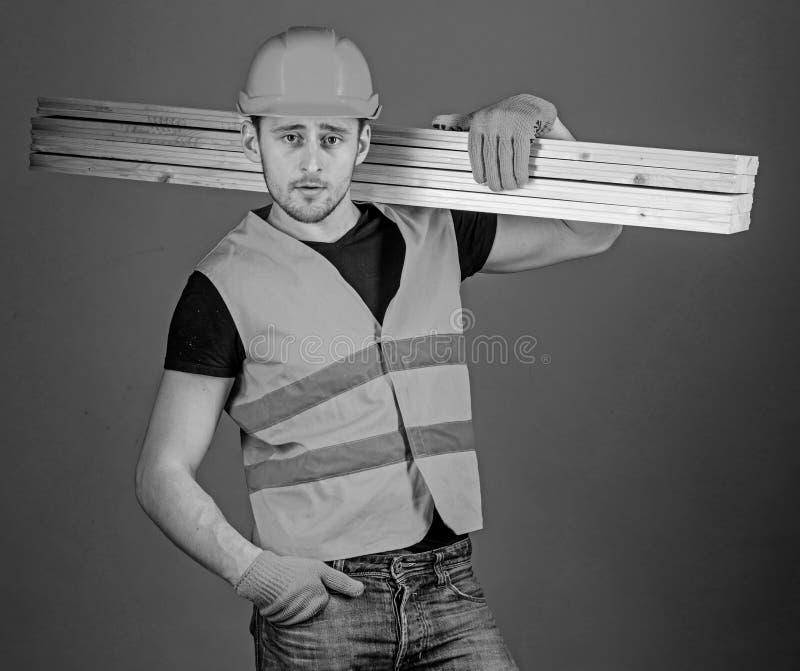 Carpenter, woodworker, labourer, builder on confident face carries wooden beams on shoulder. Hardy labourer concept. Man royalty free stock image