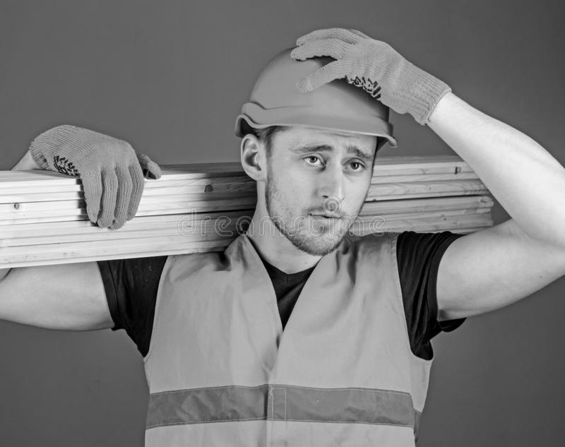 Carpenter, woodworker, strong builder on serious face carries wooden beam on shoulder. Safety and protection concept. Man in helmet, hard hat and protective stock photos