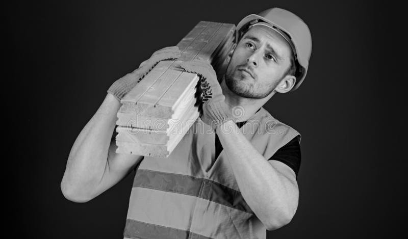 Carpenter, woodworker, strong builder on thoughtful face carries wooden beam on shoulder. Wooden materials concept. Man. In helmet, hard hat and protective stock images
