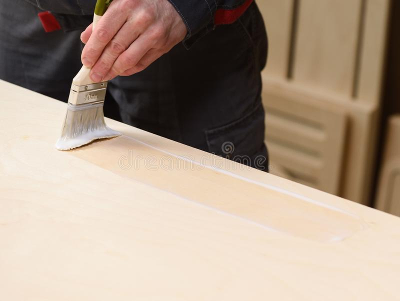 Carpenter at work. Close up of covering wooden surface by paint brush with varnish. With copy space royalty free stock image