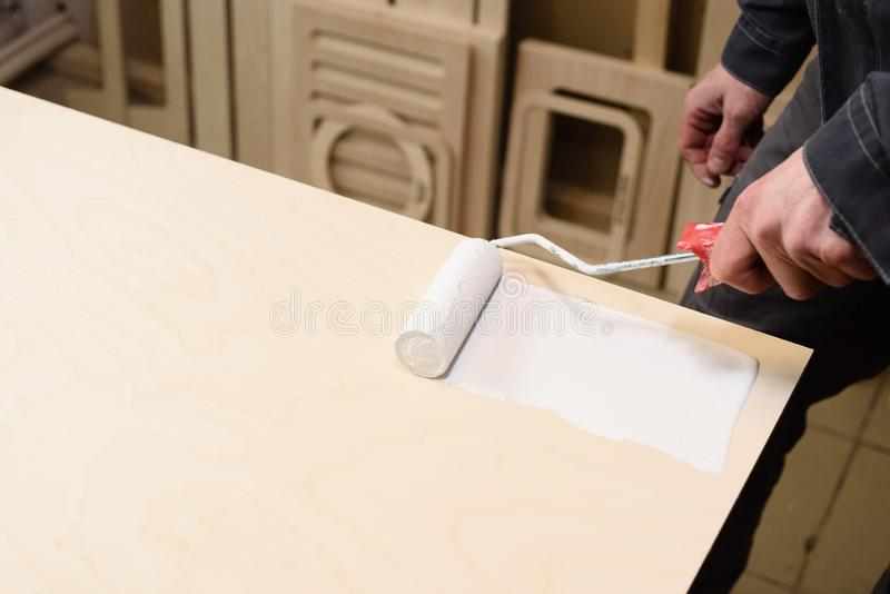 Carpenter at work. Close up of covering wooden surface white paint by paint roller copy space. Carpenter at work. Close up of covering wooden surface white paint stock image