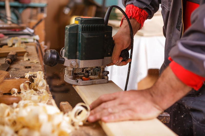 Carpenter at work with electric planer joinery stock image