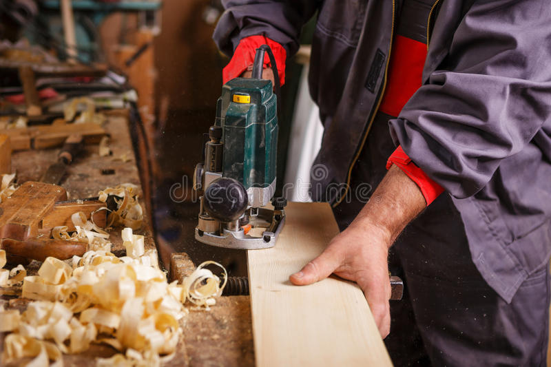 Carpenter at work with electric planer joinery. The carpenter hands when working with electric planer joinery stock photos