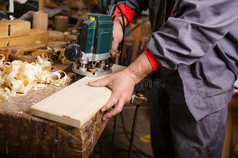 Carpenter at work with electric planer joinery. The carpenter hands when working with electric planer joinery royalty free stock photos