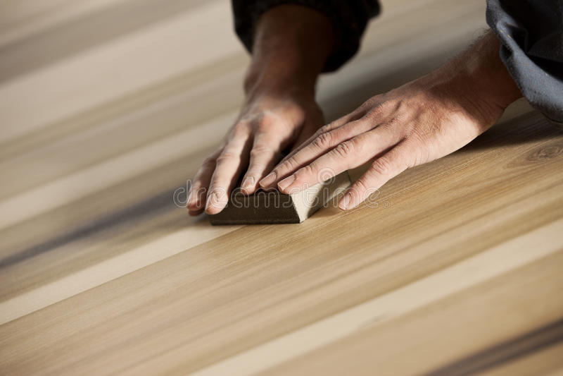 Carpenter at work. Professional carpenter sanding and refinishing wood surface stock image