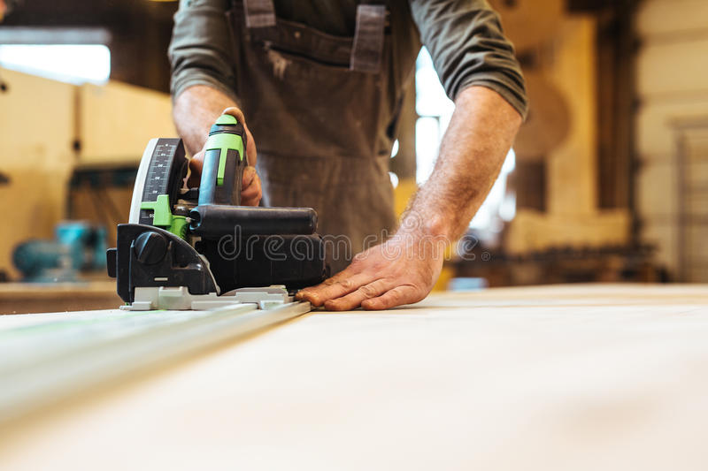 Carpenter at work. Carpenter using scroll-saw or wood-router royalty free stock photography