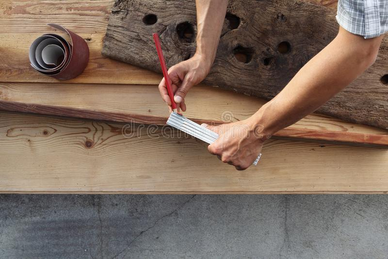 carpenter work the wood, measuring with meter and pencil old rustic wooden boards, top view background royalty free stock images