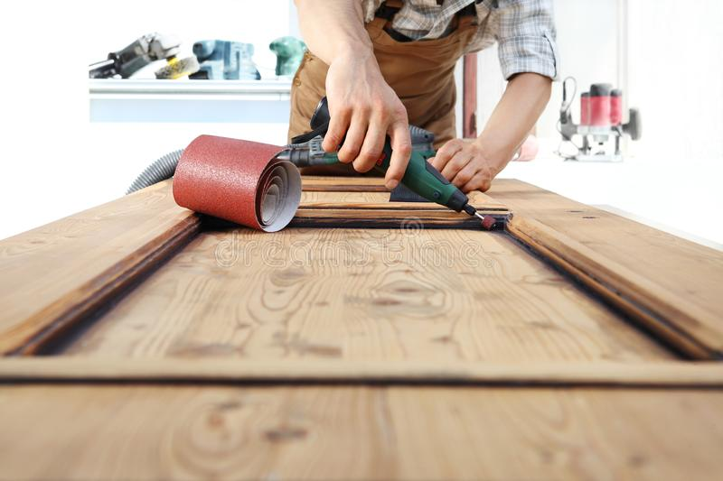 Carpenter work the wood with the rotary tool. On vintage wooden door stock photos