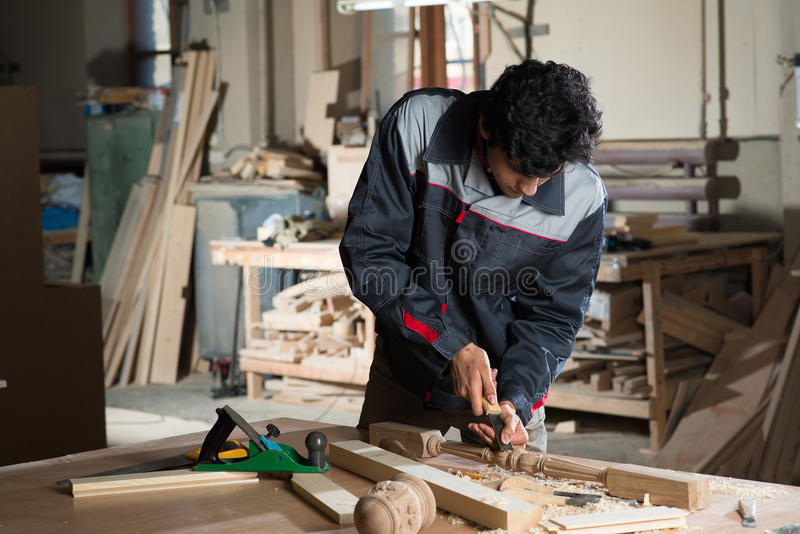 Carpenter at work. Young craftsman in uniform working at carpentry stock image