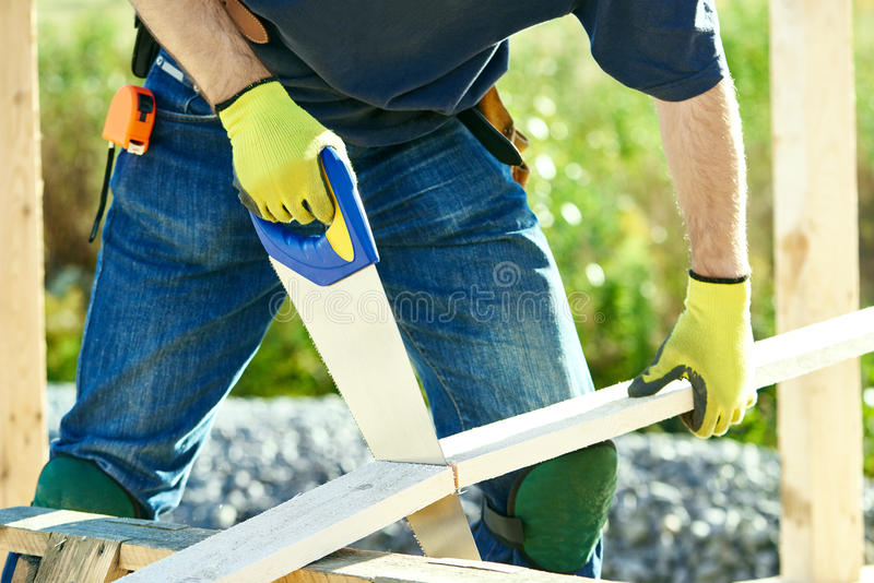 Carpenter worker cutting wood board. Closeup construction roofer carpenter worker sawing wood board with hand saw outdoors stock photography