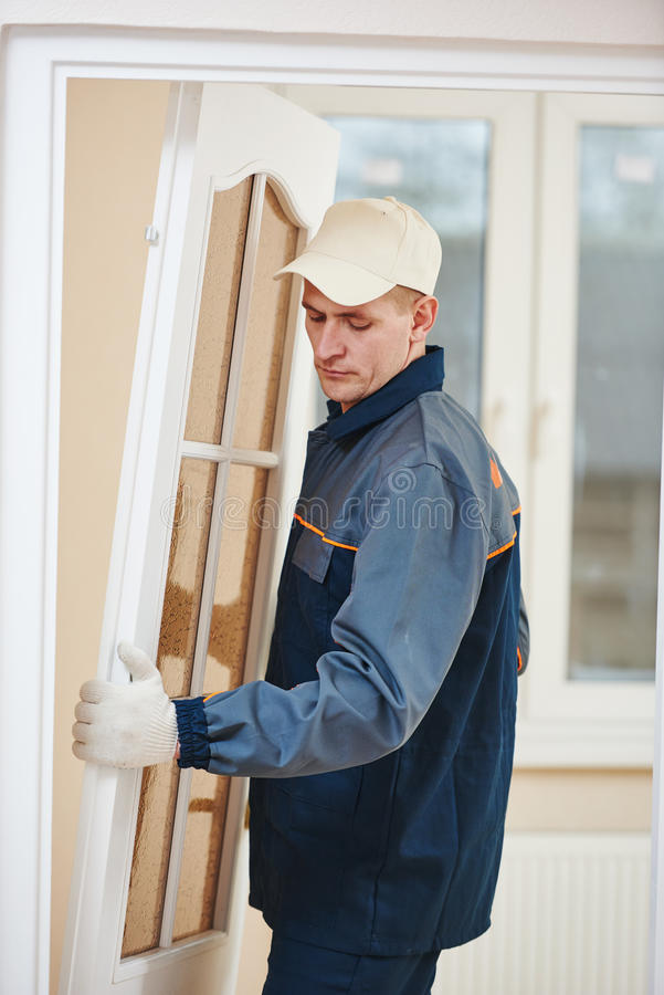 Carpenter worker at door installation royalty free stock photo