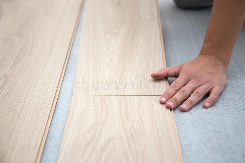 Carpenter worker installing laminate flooring in the room stock photo