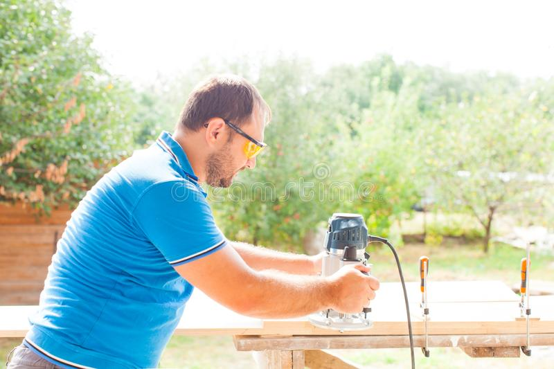 Carpenter working with electric planer on wooden plank. Carpenter wearing protecting glasses, working with electric planer on wooden plank outside near his house stock photography