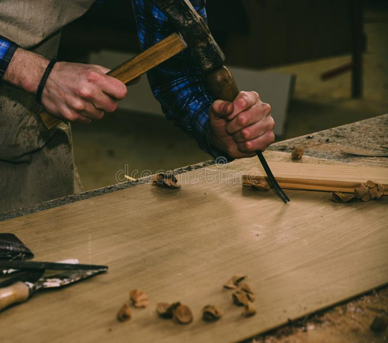 Carpenter working with hammer and chisel on wood table. Workshop background royalty free stock image