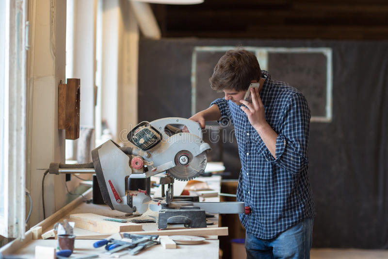 Carpenter working on his craft in a dusty workshop stock photo