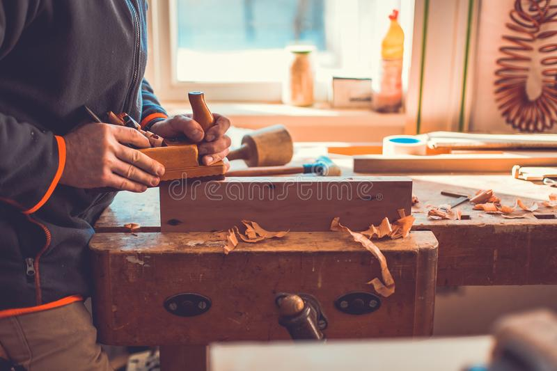 Carpenter working with jointer planing wood plank at workshop, carpenter working with plane on wooden background stock photo