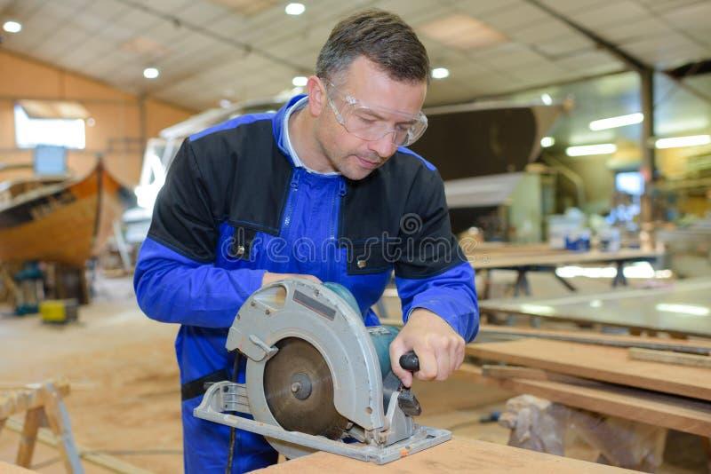 Carpenter working man cutting plank by circular saw stock images