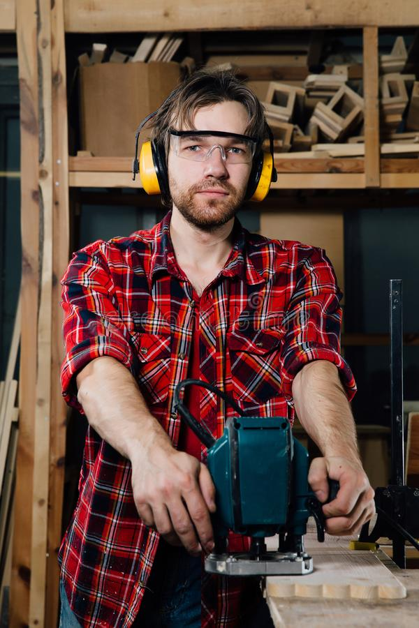 Carpenter working of manual hand milling machine in the carpentry workshop. joiner. royalty free stock image