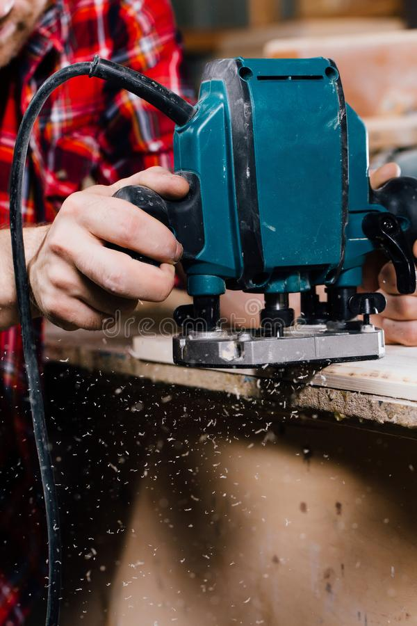 Carpenter working of manual hand milling machine in the carpentry workshop. joiner. stock photos