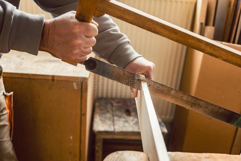 Carpenter working on wood with frame saw stock photography