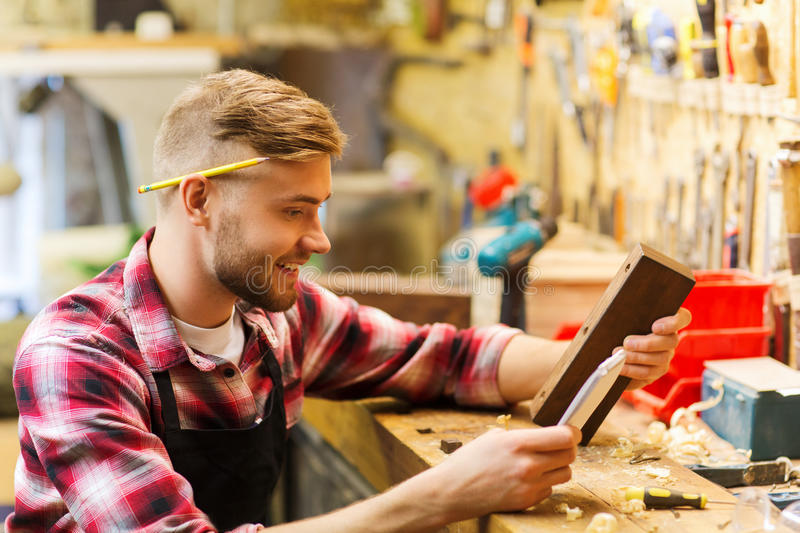 Carpenter working with wood plank at workshop stock image