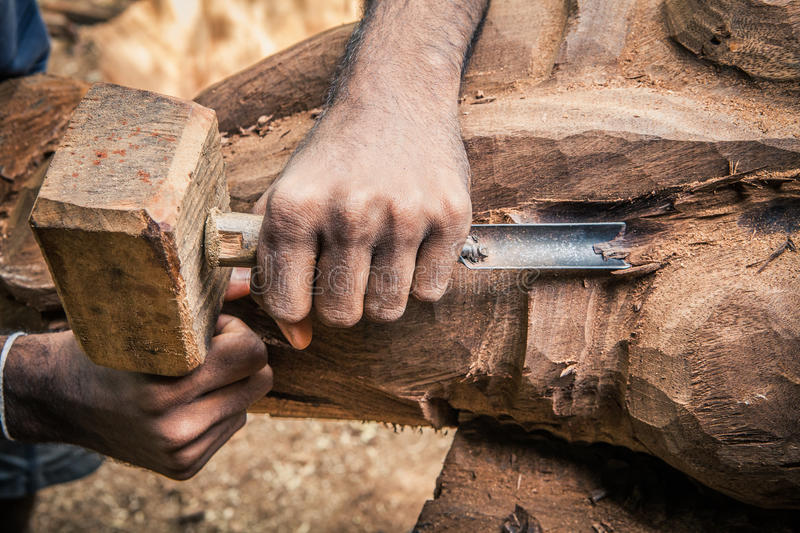 Carpenter working wood. Rudimentary tools. Two hands chiseling a piece of wood royalty free stock photo