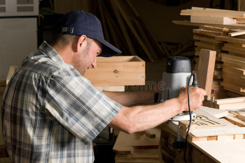 Carpenter works. Carpenter working in the woodworking shop royalty free stock images
