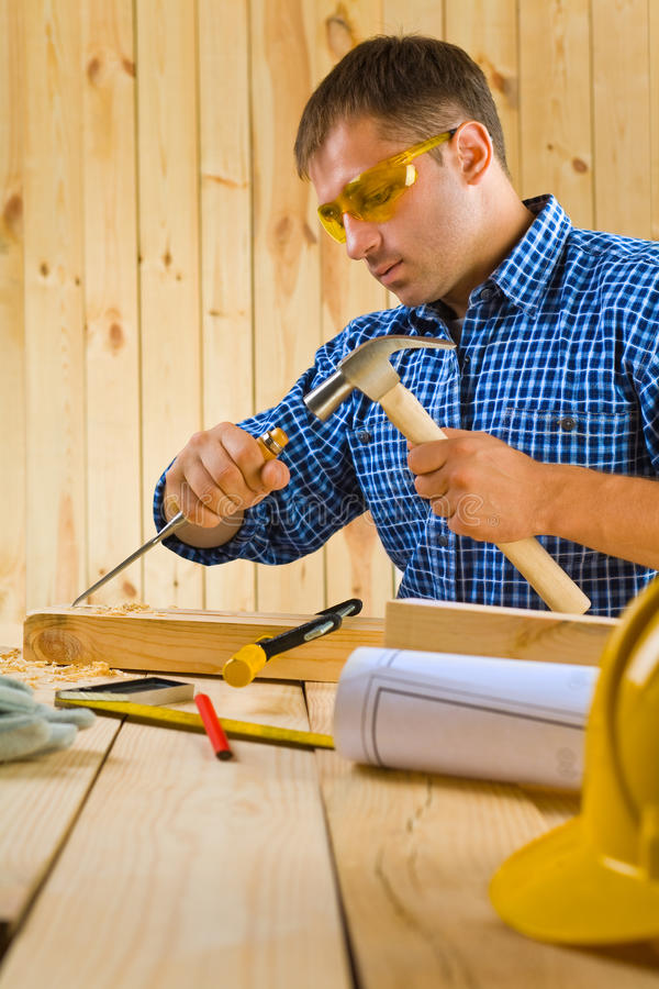 Carpenter works with the chisel stock photo