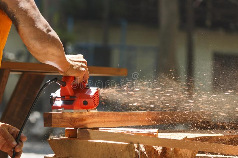 The carpenter works with the electric polisher on the wood royalty free stock photography