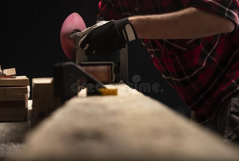 Carpenter works with electrical planer stock photos