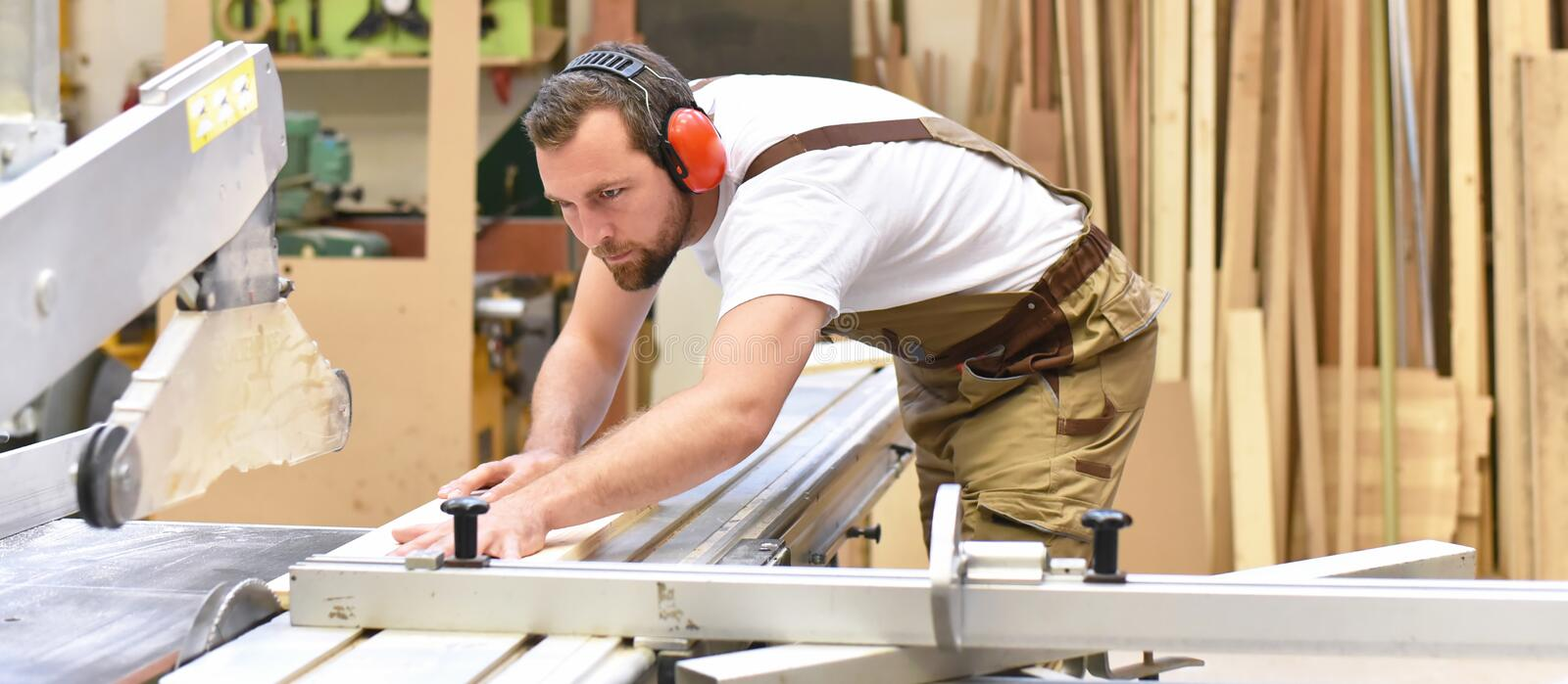 Carpenter works in a joinery - workshop for woodworking and sawing. Closeup photo royalty free stock photos