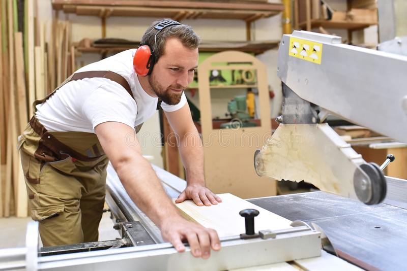 Carpenter works in a joinery - workshop for woodworking and sawing royalty free stock images