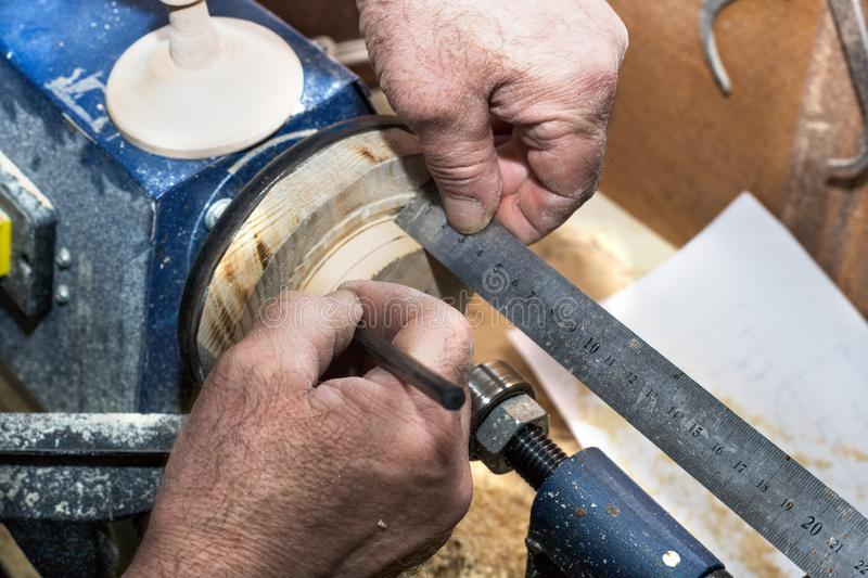 A carpenter works on a lathe on a tree. Hands with a pencil and ruler measure the product royalty free stock photos