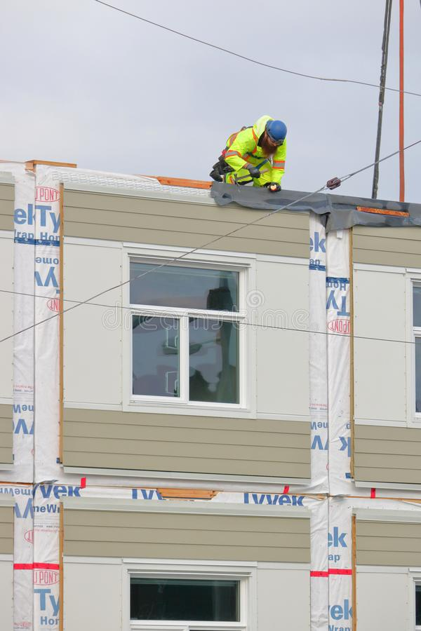 Carpenter works on modular building for homeless. A carpenter works on a portable, modular building that will provide temporary shelter for homeless people in stock photos